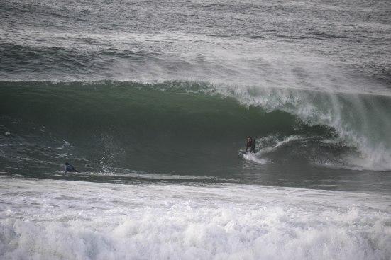 Cédric Giscos est accroupi, ce qui rend cette vague encore plus impressionnante
